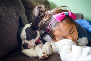 girl sleeping with dog on sofa