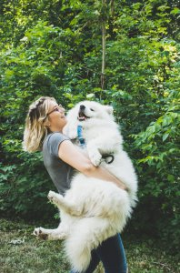 woman with glasses smiling carrying white fluffy dog